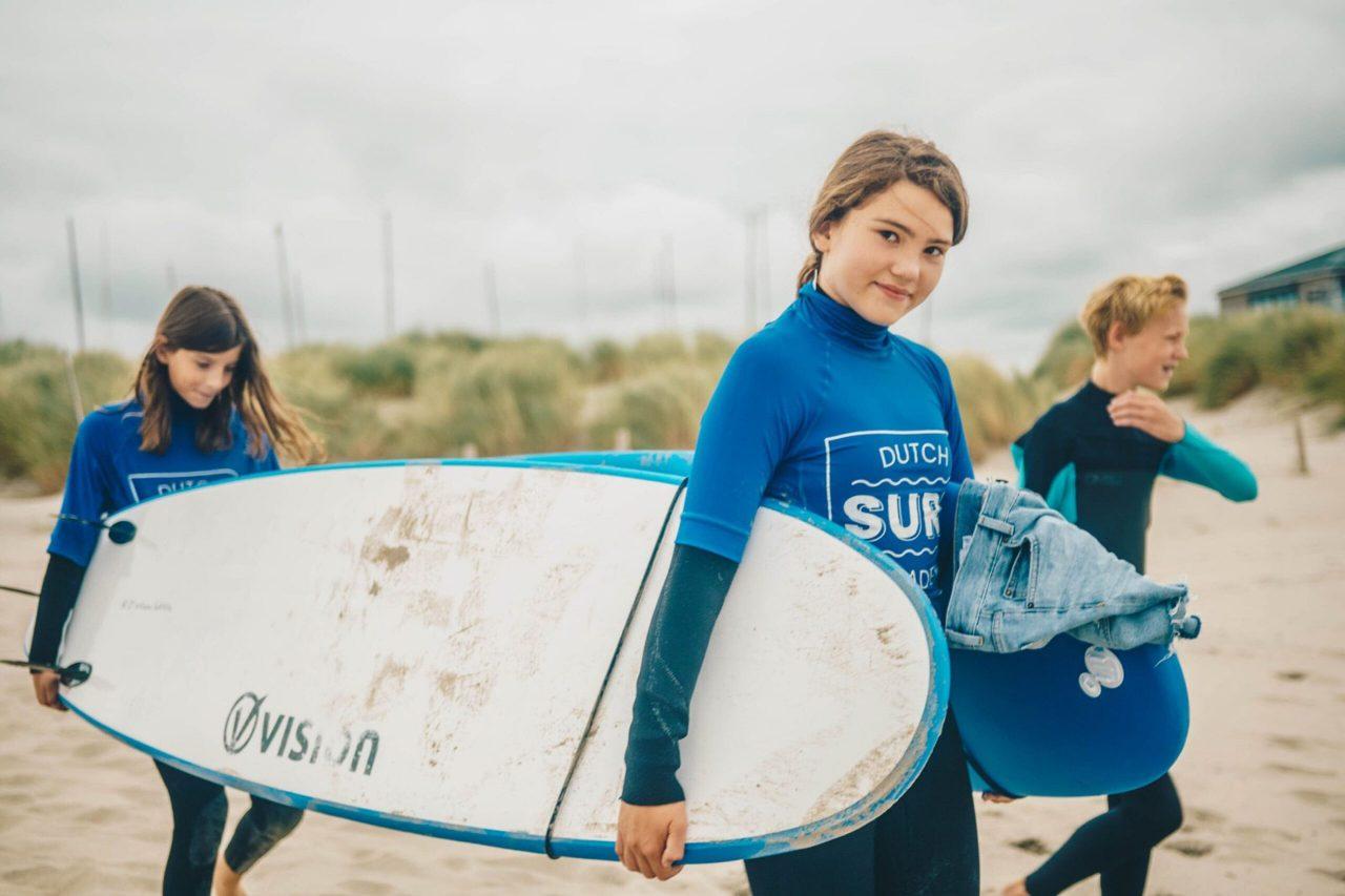 kinderen met wetsuit en surfboard