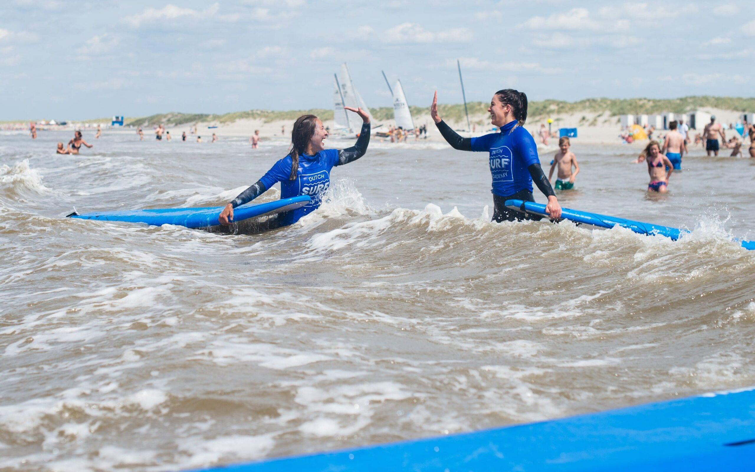 Twee surfers die van blijdschap elkaar highfiven