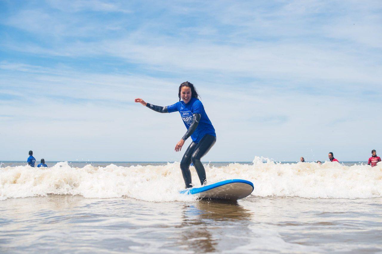 surfles lachende vrouw surfen